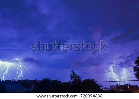 Stock Photo Bangkok, Thailand - September 22,2017 : Storm clouds with lightning strike bolts passing over night city of Bangkok cityscape. 4K Timelapse