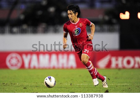 BANGKOK,THAILAND-SEPTEMBER1:Yusuke Kato (red) of BEC Tero F.C.run with the ball during Thai Premier League between BEC Tero F.C.and Insee Police Utd. at Thephasadin Stadium on Sep1,2012 inThailand
