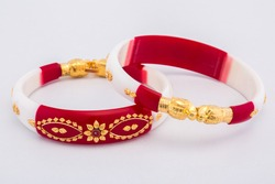 Bangle made with a gold and plastic. Isolated on white background. Jewelry stock photo. Red color bangle. Top view.