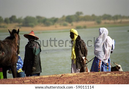 BANI RIVER, MALI - JANUARY 16: Fulani people wait for crossing the river at January 16, 2006, Bani River, Mali. Tuareg men from the desert visit the city frequently.
