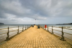 Banjo Pier looking across Swanage Bay under a cloudy sky. With two people on the vanishing point.