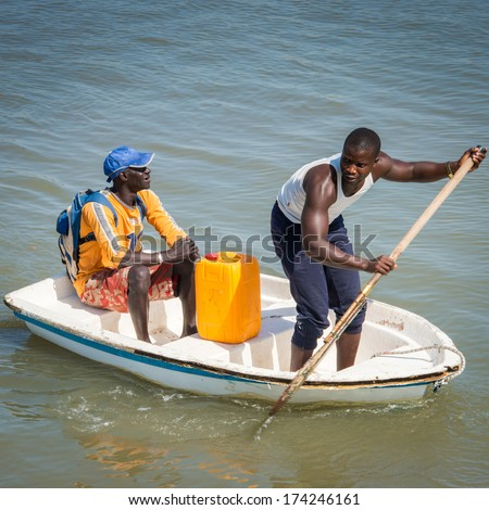 BANJUL, GAMBIA - MAR 14, 2013: Unidentified Gambian man raws a little boat with a paddle in the ocean in Gambia, Mar 14, 2013. Major ethnic group in Gambia is the Mandinka - 42%
