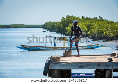 BANJUL, GAMBIA - MAR 14, 2013:Unidentified Gambian man raws a little boat with a paddle in the ocean in Gambia, Mar 14, 2013.People of Gambia suffer of poverty due to the unstable economical situation