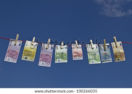 Bank notes fluttering on a clothesline against a blue sky in the wind