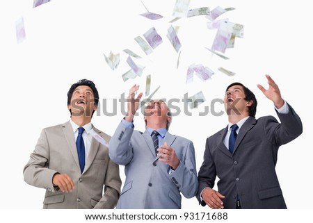 Bank notes raining down on businessteam against a white background
