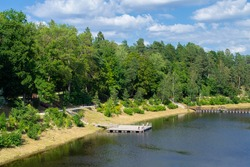 Bank of the Ogre river in the town of Ogre. The embankment is overgrown with forest and a pantone bridge across the river. Countryside and nature of Latvia.
