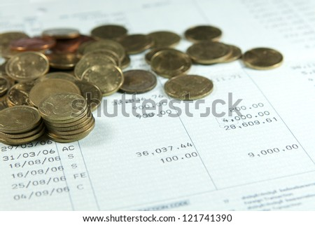 Bank saving account passbook with lot of coins