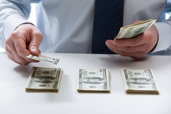 Bank teller's hands counting dollar banknotes on the table