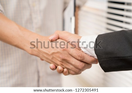 Banker business man shaking hands with client and sign contrac document for comfirm corporation or finished loan agreement for house or building property.Docum
