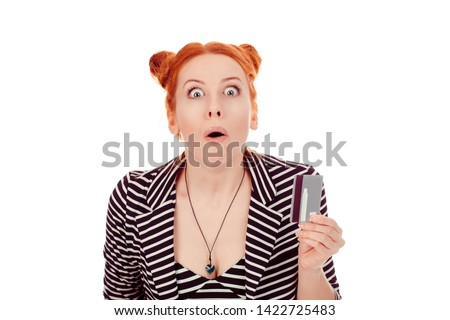 Banking shocking news. Closeup portrait of a beautiful woman shocked stunned young girl showing credit card wearing striped black white jacket with 2 buns up hairdo isolated on white background wall