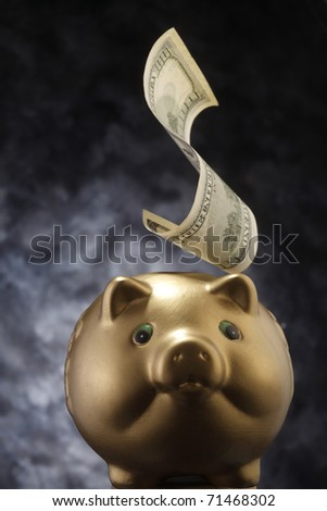 Banknote falling into the piggy bank.