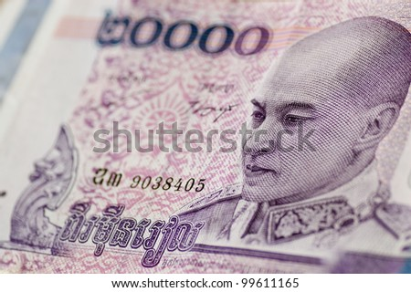 Banknote for 20,000 Riels from Cambodia showing King Norodom Sihamoni in military uniform gazing downwards.  Used banknote, photographed at an angle.