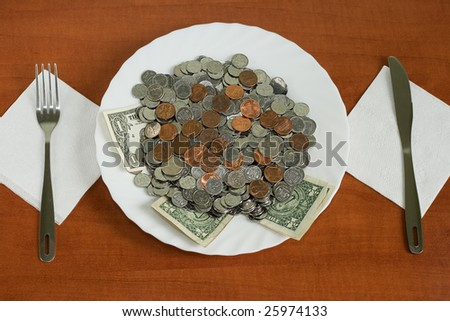 banknotes and coins on a plate with knife and fork over wooden background