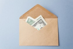 Banknotes are dollars in a paper envelope. An open envelope with banknotes on the table on a gray background. International monetary currency. Close-up. Top view.