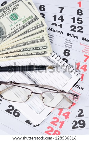 Banknotes of dollars on calendar sheets close-up