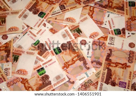 Banknotes of Russian currency face value of 5,000 rubles scattered on the table are a sign of riches and prosperity. #1406551901