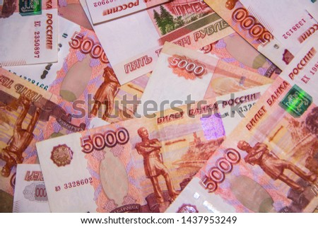 Banknotes of Russian currency face value of 5,000 rubles scattered on the table are a sign of riches and prosperity. #1437953249