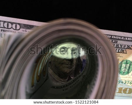 Banknotes of 100 US dollars are twisted with an elastic band. American money on the table. Benjamin Franklin's face peers out from under the hundred-dollar bills. #1522121084