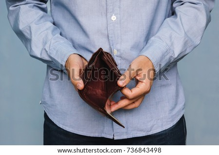 Bankruptcy - Business Person holding an empty wallet. Man showing empty wallet by showing the inconsistency and lack of money and not able to pay the loan and the mortgage.