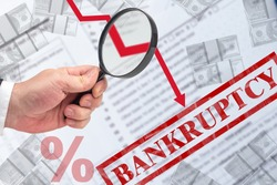 Bankruptcy due to falling incomes. Hand with a magnifier next to bankruptcy logo. Down arrow symbolizes a decrease in revenue. Decrease in profit of companies. Bankrupt. Business devastation.