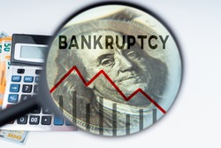 Bankruptcy of people and businesses. Falling graph under magnifying glass. Money and calculator. Concept bankruptcy law. Human bankruptcy court. Financial collapse. Failure from financial obligations