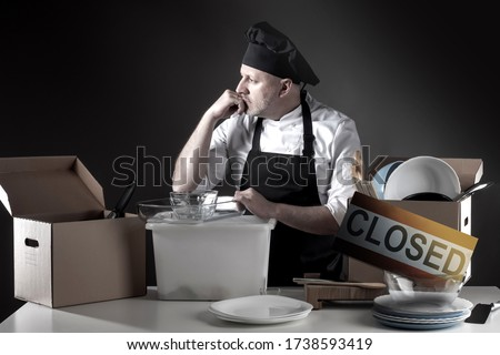 Bankruptcy. Restaurant owner overwhelmed by finance problems. Plate closed symbolizes ruin. Depressed cook closed restaurant. Horeca crisis. Dishes in boxes. Closed restaurants for COVID-19 pandemic