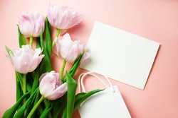 Banner. A bunch of pink tulips on a warm pink background with a card with HAPPY BIRTHDAY text and a gift bag. Flatlay