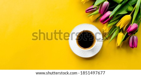 Banner.A cup of hot, morning coffee and a bouquet of yellow-lilac tulips on a bright yellow background. View from above. Close-up. Copy space for text. The concept of holidays and good morning wishes. Foto stock ©