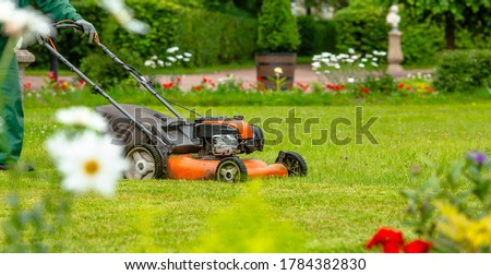 Banner. A human lawn mower mows the grass with a lawn mower in the backyard. Agricultural machinery: lawn mower for cutting grass. The care of the garden. Gardening background.