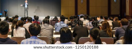 Banner and web page or cover template of Rear side of Audiences sitting and listening the speackers on the stage in low light conference hall, event and seminar concept