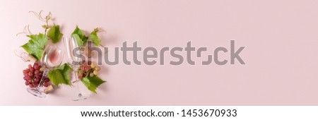 Banner 3:1. Assorted wineglasses with rose and white wine, grape, leaves and cork lying on pink background. Wine degustation concept. Flat lay. Top view. Copy space #1453670933