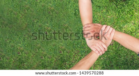 Banner Authentic triangle partners hands together concept. Three hands holding tight promise mission teamwork on green ecosystem business with copy space template.