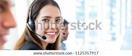 Banner background of smiling beautiful friendly woman working in call center office with team as the customer care operators