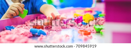 BANNER Boy playing with kinetic sand in preschool. The development of fine motor concept. Creativity Game concept. Long Format.
