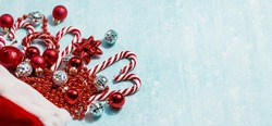 Banner. Christmas hat of Santa Claus, with Christmas candies, toys and sequins on a blue background. Minimal Christmas concept. Caramel cane. Copy of the text space.