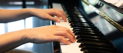 banner close up picture of hand of young woman playing piano at home