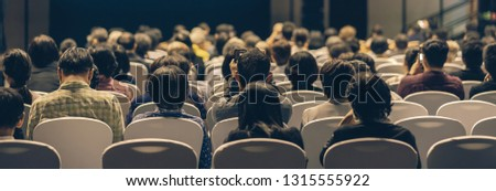 Banner cover page of Rear view of Audience listening Speakers on the stage in the conference hall or seminar meeting, business and education about investment concept