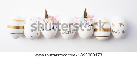 Banner. Easter eggs in the form of a unicorn, and with a gold pattern on a white background. Flat lay. Copy space for text.