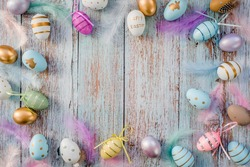Banner. Easter frame with eggs and feathers on a blue wooden background. The minimal concept of Easter. Top view. An Easter card with a copy of the place for the text.