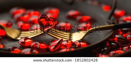 Photo of  Banner. Festive table setting.Heart on a fork close-up. Holiday concept. Valentine's Day. Copy space for inscriptions.