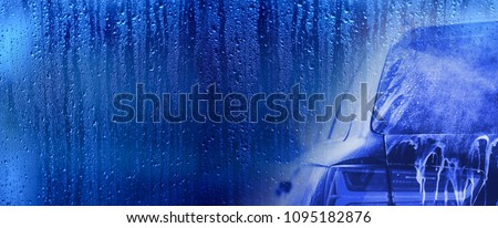 Banner For Car Wash Business. Cool Blue Background with Vehicle During Washing Process. Left Side Copy Space. #1095182876