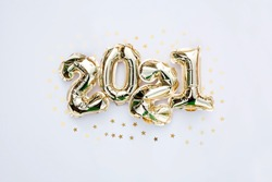 Banner. Happy New year 2021 celebration. Gold foil balloons numeral 2021 and gold confetti on white background. Flat lay.
