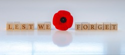 Banner Lest we forget, text on wood blocks with a poppy flower. Concept: Remembrance Day.