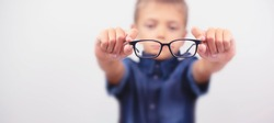 Banner little boy with glasses correcting myopia close-up portrait. Ophthalmology problem. Selective focus