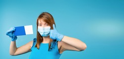 Banner,long format. A blonde girl in a medical mask and gloves shows like, passport and tickets to the camera. Monochrome blue background and side space for text or advertisement. High quality photo