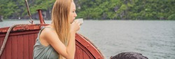 BANNER, LONG FORMAT Attractive woman in a dress is drinking coffee, traveling by boat in Halong Bay. Vietnam. Travel to Asia, happiness emotion, summer holiday concept. Picturesque sea landscape. Ha