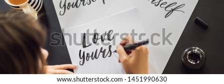 BANNER, LONG FORMAT Love yourself. Calligrapher Young Woman writes phrase on white paper. Inscribing ornamental decorated letters. Calligraphy, graphic design, lettering, handwriting, creation concept