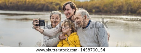BANNER, LONG FORMAT Senior couple with with grandson and great-grandson take a selfie in the autumn park. Great-grandmother, great-grandfather and great-grandson