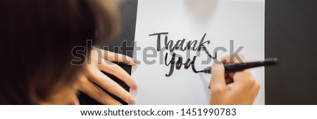 BANNER, LONG FORMAT Thank you. Calligrapher Young Woman writes phrase on white paper. Inscribing ornamental decorated letters. Calligraphy, graphic design, lettering, handwriting, creation concept