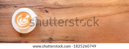 Banner made from cappuccino with frothy foam, white coffee cup top view closeup on wooden background. Flat lay style. Stok fotoğraf ©